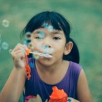 girlyoungsiblingwomanbubblesoutdoorsoutsideplaykidfunsummergrassfeaturedimage