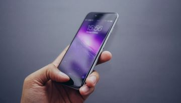 A hand holds an iPhone, which has a cosmic purple lock screen.