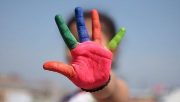 """A child gestures """"Stop"""" with their hand obscuring their face. The palm of their hand is painted in different colors."""