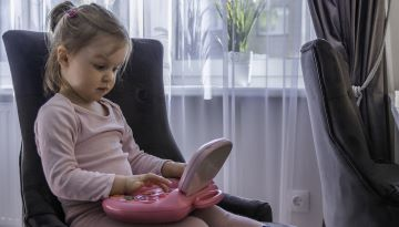 A toddler sits on a chair at home, playing with a computer toy.