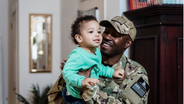 A person in military camouflage holds a toddler. They are both smiling.