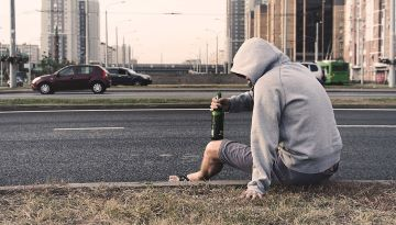 A person sits on the side of the road holding an alcoholic beverage bottle.