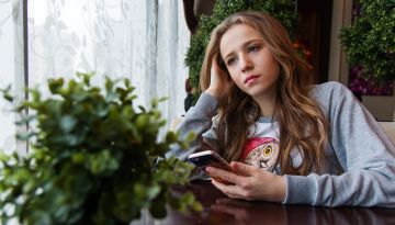 A teen girl holds her phone and looks wistfully out a window.