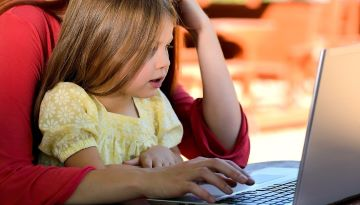 A toddler sits on her parent's lap as her parent uses a laptop.