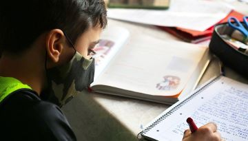 A young student sits at a table wearing a cloth face mask. He has a textbook open in front of him and writes in a notebook.
