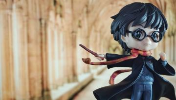 A Harry Potter toy is posed against a stone pathway like Hogwarts.