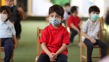 Young students sit in a classroom. They wear cloth face masks. Their seats are socially distanced.