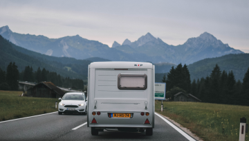 An RV drives along a highway. There are mountains in the background.
