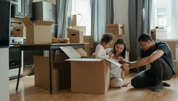 Two parents and a child are surrounded by packing boxes as they prepare for a move.