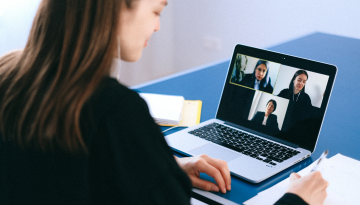 A person takes notes during a video meeting. Colleagues appear in little boxes on a laptop screen. All are smiling.