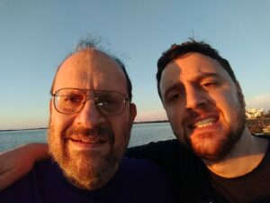 Arthur Henick and his adult son Ian smile at the camera. In the background is a body of water and a dark blue sky.