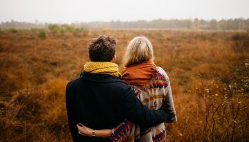 Two people stand closely together in a field in the autumn. They have their arms around each other.