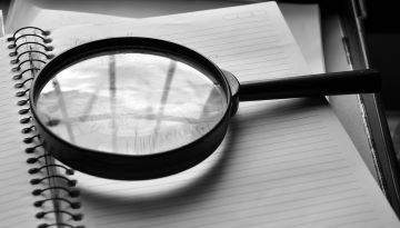 A magnifying glass lays on a lined page from a notebook.