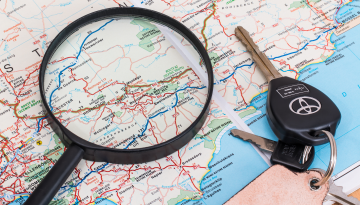 A road map lays in the background. A magnifying glass and a set of car keys are placed on top of it.
