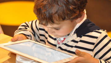 A preschool-age child holds an iPad and stares at it with engaged focus.