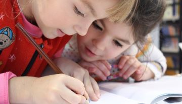 Two young students work together. One writes in a notebook while the other closely watches.
