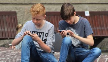 Two teenagers stare intensely at their smartphones while touching the phones' screens.