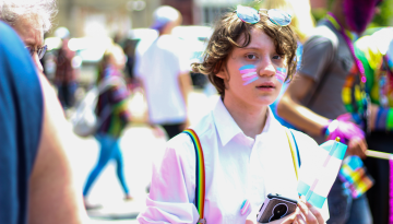 A young person glances at the camera. They wear face paint in blue, white, and pink, representing the trans flag. They wear rainbow suspenders, representing the LGBTQIA+ community. They hold a small trans flag.