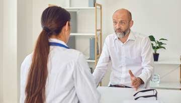 A middle-aged man sits at a table and speaks to a doctor. He has a serious expression.