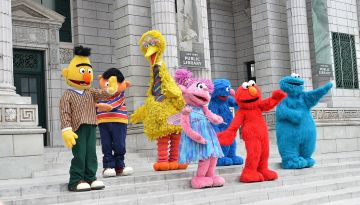 A group of Sesame Street mascots stand outside a building and wave. Characters include Bert, Ernie, Big Bird, Abby Cadabby, Elmo, Grover, and Cookie Monster.
